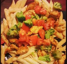 Penne noodles with strips of chicken topped with broccoli diced tomatoes and sprinkles with Cajun seasoning.