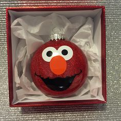 Elmo ornament. His face was cutout of vinyl using a cricut and the ornament was made using mop and glo and red glitter.