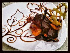 Bizcocho casero de melocotones, con salsa caliente de chocolate negro.