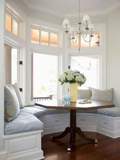 When wall space is at a premium, windows make great backdrops for bench seating. Here, a banquette tucks snugly into a sunlit bay window to take advantage of often-unused space. The result is a formal dining room feel that uses up only one wall of the kitchen. In addition to abundant seating, the bench features lower drawers that provide storage for table linens and other dining room accessories.