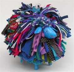 Papier mache animal embellished with yarns, felt and fabrics.