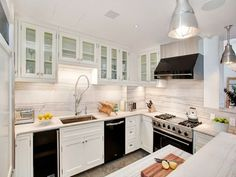 how to decorate a kitchen with black appliances. Shown with white painted cabinets