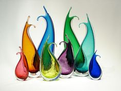 """The graceful curve of these vases makes them interesting on their own, but even more beautiful together. Small: 6"""" Medium: 9"""" high with crackle finish, Large: 12"""" high with tiny bubbles. Available colors - Colors: Ruby, Sienna, Topaz, Chartreuse, Green, Aqua, Marine Blue, Teal, Reddish Amethyst, Cobalt, Hyacinth."""