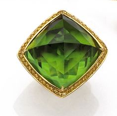 A peridot and colored diamond ring  centering a faceted pyramid-shaped peridot weighing 48.00 carats, within a surround and shoulders of yellow round brilliant-cut diamonds; estimated total diamond weight: 2.00 carats; mounted in eighteen karat gold.