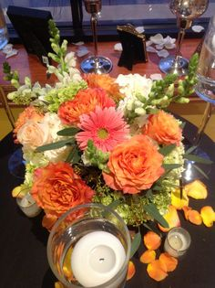 Wedding centerpiece of white hydrangea, Free Spirit roses, white snap dragons, peach roses, mini green hydrangea, coral gerbera daisy, and seeded eucalyptus