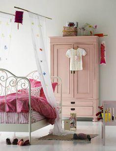 Romantyczny pokój z bogato zdobionym metalowym łóżkiem to marzenie niejednej małej dziewczynki. Stylu dodają białe zasłonki z aplikacjami kolorowych motyli  zawieszone nad łóżkiem na wzór baldachimu. Kropką nad i jest starodawna drewniana szafa pomalowana na różowo.