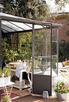 A beautifully styled, light-filled wrought iron greenhouse, as featured on El Mueble.