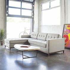 The Gus Modern Jane Bi-Sectional Sofa - Walnut has all the tailored good looks of the original Jane--but with a wooden update. While maintaining the clean lines established by the original stainless steel base, the Walnut-finished wood base adds definite warmth to the overall look. Like all the other cushions, the chaise cushion is button-tufted on both sides, so can be flipped and placed on the right or left as needed.