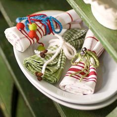 For casual, homespun embellishments, wrap yarn around rolled napkins, tie with bows, and slip on felt beads, miniature pinecone ornaments, or jingle bells! http://www.bhg.com/christmas/indoor-decorating/festive-holiday-napkin-ideas/?socsrc=bhgpin122014yarntiednapkin&page=26