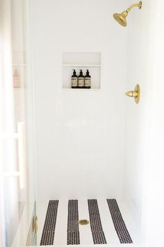 Striped penny tile for a shower floor. Gold fixtures. White tile surround. Simple and beautiful.