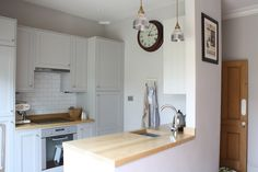Predominantly white kitchen painted in Cornforth White with metro tiles and butcher block countertop