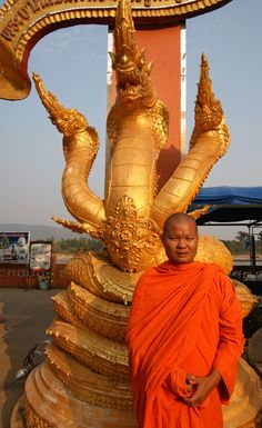 A monk poses by a statue in the Golden Triangle, a spot where the borders of Thailand, Myanmar and Laos meet.