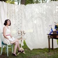 Hanging vintage lace tablecloths make for a wonderful backdrop in an outdoor wedding