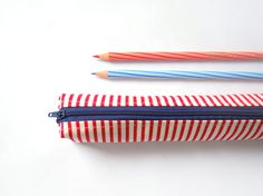 Small pencil case/zipper pouch in red and white stripes, with a dark blue zip and a cobalt blue lining