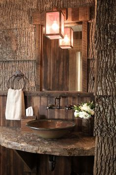 Woodsy rustic Powder Room with bark siding walls, bowl sink on slate countertop, and pendant lantern...