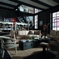 Living room urban loft style with beige couch, grey classical armchair and black floors by Dialma Brown. |  Salon au style urbain et au style loft avec un canapé beige, un fauteuil gris et un sol noir, par Dialma Brown