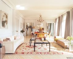 Parisian apartment with multiple sofas and coffee tables, Persian tug, and crystal chandelier