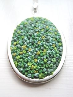 french knot.  Since this is in a locket frame, I would try to find an appropriate brooch or pin, etc. to put on it.  Would be a VERY intriguing background.