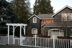 gray house, white fence, lovely arbor (and curved windows) House Paint Exterior, Exterior House Colors, Dark Grey Houses, Arbor Gate, Exterior Color Schemes, White Fence, Front Yard Landscaping, House Painting, My House