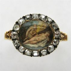 A GEORGIAN PAINTED DIAMOND CLUSTER RING    A Georgian diamond cluster ring, the central oval-shaped hand painted section depicting a faun and naked lady, set to the centre of an old-cut diamond cluster surround, all set in silver to a yellow gold back, to a tapered D-section yellow gold shank, gross weight 3.2 grams, circa 1790