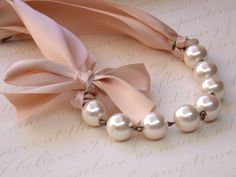 Carrie Bradshaw  Inspired Pearl Necklace In Nude Color Satin Ribbons. Perfect for Bride, Wedding, Bridesmaids And Formal. $39.00, via Etsy.