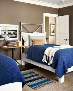 The guest room's headboards are actually salvaged iron gates, attached to platforms from Simply Home. Bartkowski captured the image—one of her favorites—in the Tuileries Garden in Paris. The walls are painted Buckhorn by Benjamin Moore. - CountryLiving.com