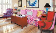 """Jeffrey Bilhuber -  The family room sofa is dressed in China Seas' Macao II to match the valances and is complemented by colorful throw pillows in Quadrille and Malabar fabrics. A custom """"extended carpet"""" chair with turned wooden legs is also covered in John Robshaw's Vintage Stripe."""