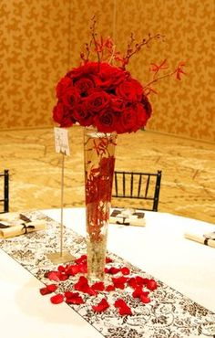 Large, tall centerpiece featuring red roses and james story orchids