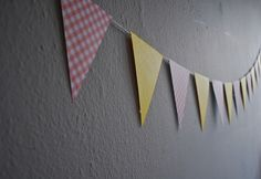 One of the simplest pennant banner instructions I've seen. I'm thinking of making these for my daughter's birthday party rather than expensive and annoying balloons. To hang, just put up a couple of thumb tacks for each banner.