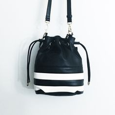 SALE‼️Black&White Faux-Leather Striped Bucket Bag Super cute and very trendy! The front has a black and white stripe pattern. Comes with a shoulder strap and a short strap. Shoulder strap is detachable and adjustable. Lining is a black and white stripe. MAKE ALL OFFERS THROUGH THE OFFER BUTTON & NO TRADES Boutique Bags