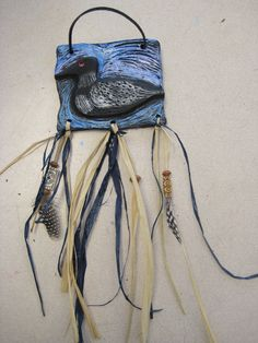 clay relief tile with animals, painted first in black tempera, then dry brushed with metallic tempera paint, suede strap for a hanger, and raffia, beads, and feathers tied on to the bottom