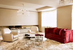 This luxurious living room combines bronze, subtle golds and a pop of red to create a glamorous space. The lush cream walls act as a plain canvas for the deluxe two-seater, red sofa accessorised with plump red cushions. The mirror finish coffee tables feature a transparent vase filled with bright roses. #livingroom #livingroomideas #luxurylivingroom #redsofa #sheercurtains #chandelier #contemporary