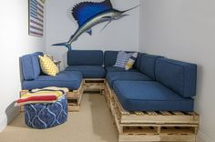 A blue couch around the corner provides extra sitting space. Inspired by a couch they saw at Benni's, they created this setup out of wood pallets and reupholstered outdoor cushions. [Perfect for basement or garage playroom! -UDG]