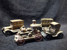 REPRODUCTION METAL CAR TOY BANKS, LOT OF THREE WITH A FOURTH THAT IS MISSING A WHEEL. MARKED BANTHRICO. CIRCA 1970S