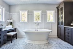 Elegant black and white bathroom features a roll top bathtub paired with a polished nickel tub filler placed on gray marble basketweave floor tiles beneath three window framed by board and batten and light gray upper walls complementing a curved shiplap ceiling.