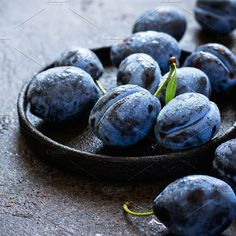 Dark blue plums in cast iron plate on black background closeup Photos Dark blue plums in cast iron plate on black background closeup. by colnihko