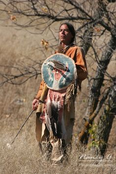 A Native American man standing with a weapon with a shield. Nancy Greifenhagen Photography
