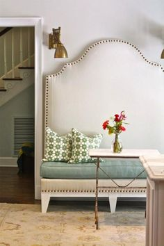 Gorgeous DIY padded camel back bench with French brass tacks, blue cushion, white & green pillows, brass sconces, brass table with marble top and Oriental rug.