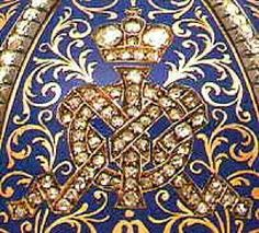 """The gold egg is covered w/6 blue champlevé enameled panels, each panel being divided by bands set w/rose-cut diamonds, gilt w/scrolls, and decorated w/the Imperial crown and the Imperial monograms """"MF"""" and """"AIII,"""" which are set in rose-cut diamonds, each monogram appearing 6 times; a portrait diamond surrounded by smaller diamonds surmounts the egg and another is set under the egg. Marie Fedorovna's monogram appears on the top half of the egg, Alexander III's, on the bottom half"""