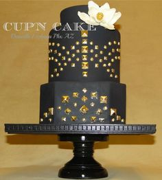 I made this cake for the cakes décor fashion inspired cake contest. Black fondant with edible gold leaf fondant studs and gum paste magnolia, I used chocolate ganache for this cake and loved the sharp edges I was able to achieve with it. Thanks for looking!. This is a real cake because Im running out of room to store dummies lol. my awesome hubby made me the cakestand :)