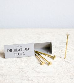 catbird•Equilateral Triangle Nails :: Solid bronze decorative triangular nails - perfect for hanging jewelry, keepsakes and photos. Sold in set of 4. Set includes a 5th nail to be used to make a pilot hole. Hand cast in the US. – $28