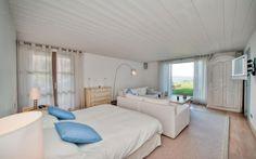 Schlafzimmer im Landhausstil mit weißem und hellem Holz und hellblaue Akzent