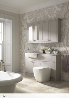 The natural light is key to this feminine bathroom idea. Soft muted tones with an oversized textured damask wallpaper, fresh flowers, warm travertine floor tiles and beautiful panelled Georgian windows. Painted shaker vanity and furniture provide essential bathroom storage solutions. Photography by http://www.setvisionspix.co.uk/. Great idea for home renovation