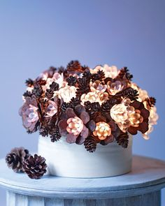 "Pinecone ""flowers"" with glowing centers fill a simple vase in this exquisite arrangement. For the petals, snip woody scales from pinecones, and glue them to plastic flowers on specialty string lights. Arrange the lights in a vase, and add tiny pinecones on wire stems for a lush, compact bouquet. Set it on a side table or a mantel for easy cord-hiding."