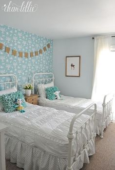 This Whimsical Enchanted Woodland Wallpaper adds a perfect backdrop to this vintage style little girls room. The ruffled aqua pillows help add a modern touch to the antique style iron beds.