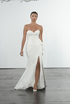 This satin gown from the new Dennis Basso for Kleinfeld Fall 2018 bridal collection features a strapless sweetheart neckline, draped skirt with thigh-high slit, sheath silhouette, and side waist tie.