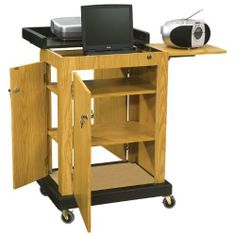 """Oklahoma Sound SCL-OK Smart Cart Lectern, 28"""" Width x 41"""" Height x 21"""" Depth, Light Oak by Oklahoma Sound. $299.63. Our computer friendly lectern is a multipurpose computer lectern cart featuring a 2"""" deep area for a laptop that locks with a slide out locking shelf for projectors and multimedia equipment. Three locking doors provide secure storage on three inner shelves for equipment and A/V material. Wire management grommets are strategically fixed inside the unit for la..."""