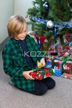 boy opening his christmas gift. - Happy boy receives gift on Christmas day.  Model: Josh Chapman
