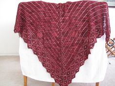 """This is a triangular shawl that is knitted from the bottom point of the """"triangle"""" upwards. The advantage of this is that you can make the shawl any size you like: just stop adding rows when you feel it's done. The main part of the shawl features a stylized cable running down the center, with parallel rays going off to the right and left. This look was directly inspired by the so-called Greek Geometric Period in pottery, which is why I named the shawl Greek Revival."""