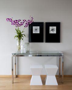 E que tal esse aparador de vidro no hall? Com os quadros e as flores o ambiente ganhou um estilo moderno e descontraído ;)